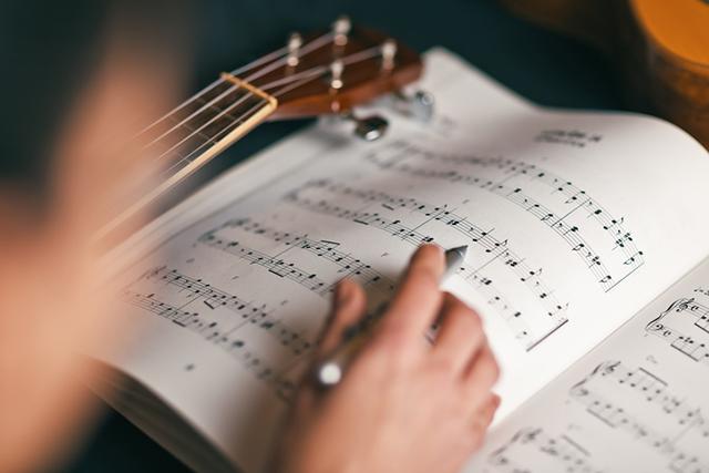 Person analysiert Noten eines Musikstückes