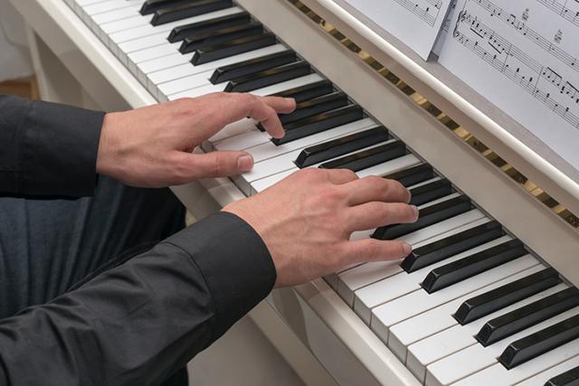 Mann spielt Klavier mit Noten