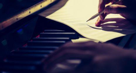 Leeres Notenblatt wird auf Klaviertastatur beschriftet