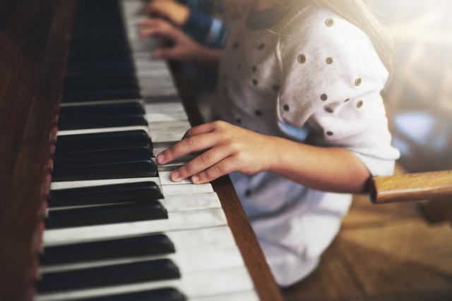 Kind spielt als Anfänger Klavier